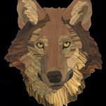 """Red Wolf intarsia, 2016. 50 pieces, 6.8""""w x 8.6""""h Mahogany, Cherry, Spalted Maple, Walnut, Cocobolo, Hickory, Marblewood, Mango, Bocote, Gaboon & Macassar Ebony, Olivewood, and Yellowheart."""